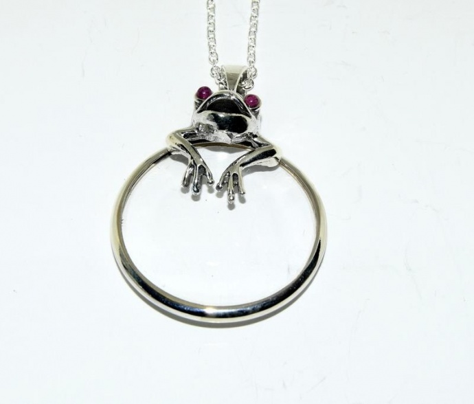 Silver magnifying glass in the form of a pendant necklace with frog finial.